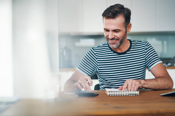 Smiling man using notebook and calculator to manage home budget stock photo