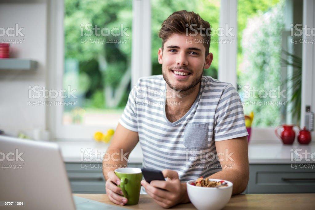 喝咖啡時使用電話的男人微笑著 免版稅 stock photo