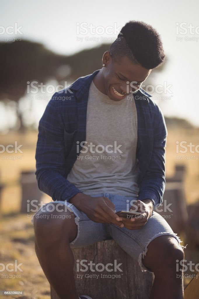 Smiling man using smart phone while sitting on tree stump royalty-free stock photo