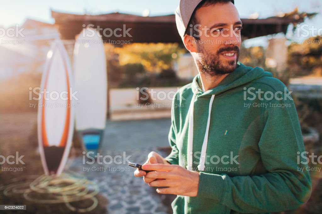 Smiling man using smartphone stock photo