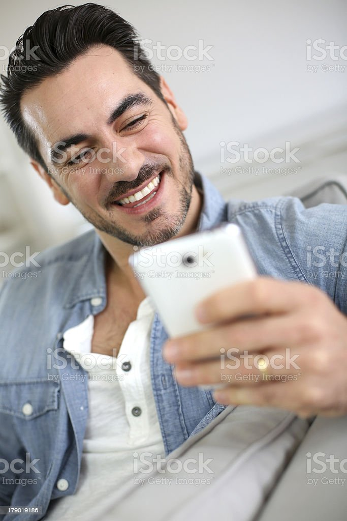 Smiling man using smartphone sitting in sofa royalty-free stock photo