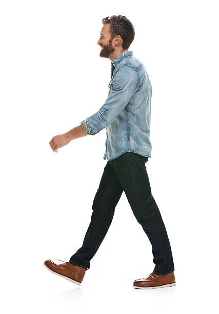 Homem sorridente caminhando e olhando longe - foto de acervo