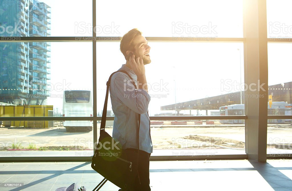 Smiling man walking and talking on mobile phone at station stock photo