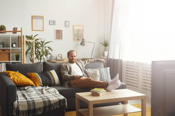 Smiling Man Watching TV at Home Full length portrait of modern adult man relaxing on couch while watching TV at home, copy space bachelor stock pictures, royalty-free photos & images