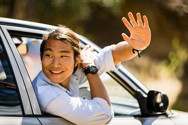 smiling man waving hand from car window - homme faire coucou voiture photos et images de collection