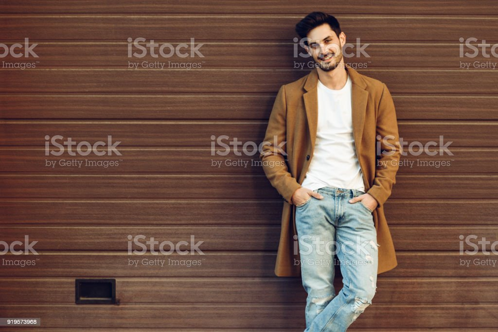 Smiling man wearing demi-season clothes in the street. stock photo