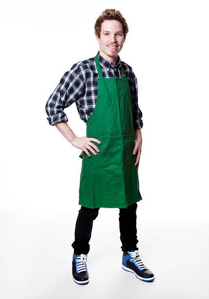 smiling man wearing green apron - groenteboer stockfoto's en -beelden