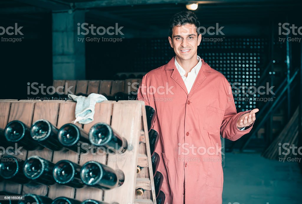 smiling man wearing uniform working with bottle storage racks stock photo