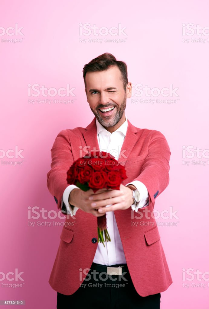 Smiling man winking and giving bunch of roses stock photo