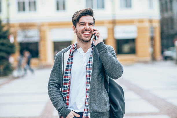 smiling man with a cell phone on the street - violetastoimenova stock photos and pictures