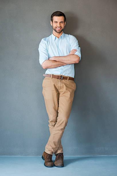 smiling man with arms crossed facing the camera - preppy fashion stock photos and pictures