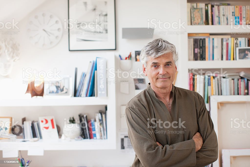 Smiling man with arms crossed in home office stock photo