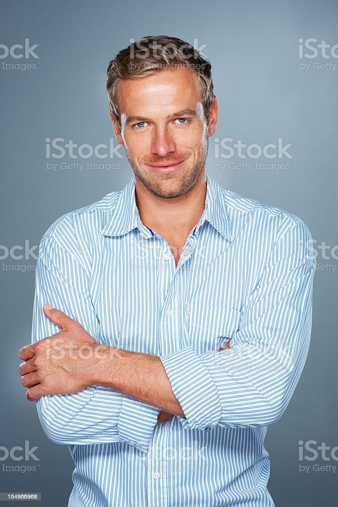 Smiling man with arms folded stock photo