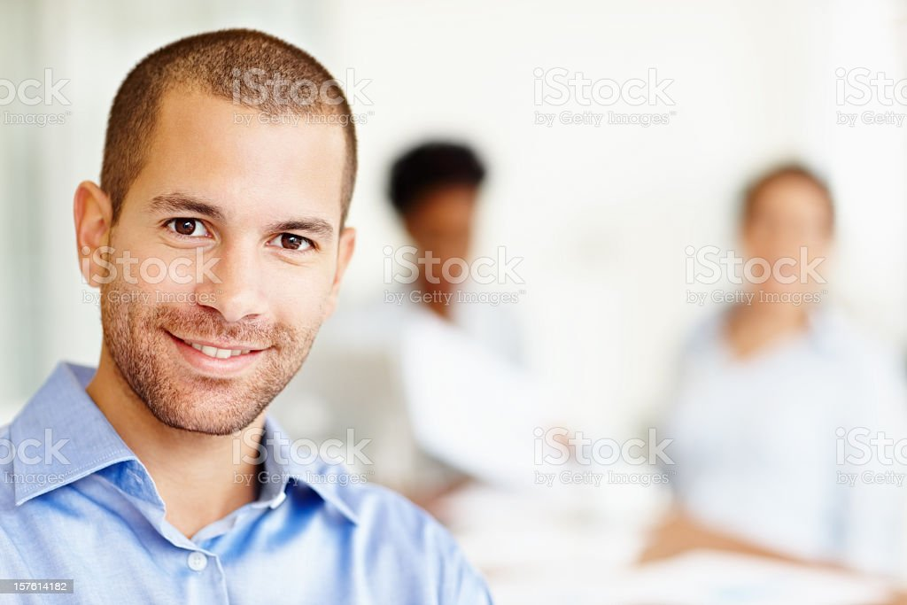 Smiling man with blurred colleagues in the background royalty-free stock photo