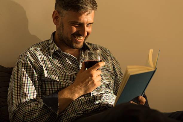 lächelnder mann mit buch - kurzgeschichten stock-fotos und bilder