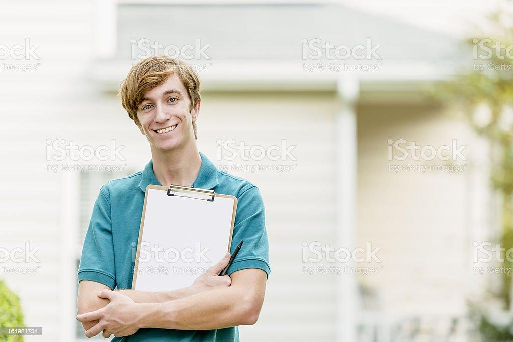Smiling man with clipboard doing door to door canvassing stock photo