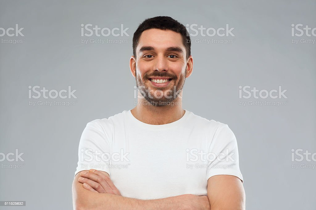 emotion and people concept - happy smiling young man with crossed...