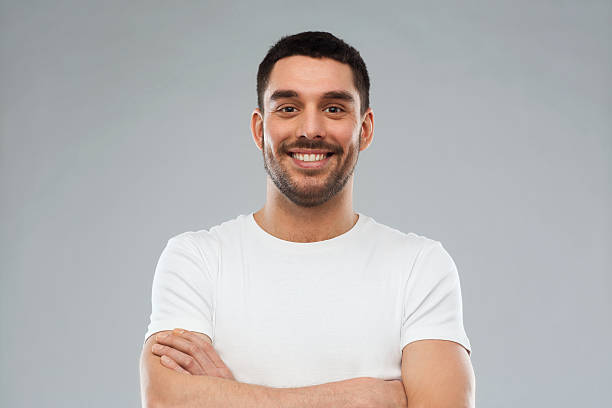 smiling man with crossed arms over gray background stock photo