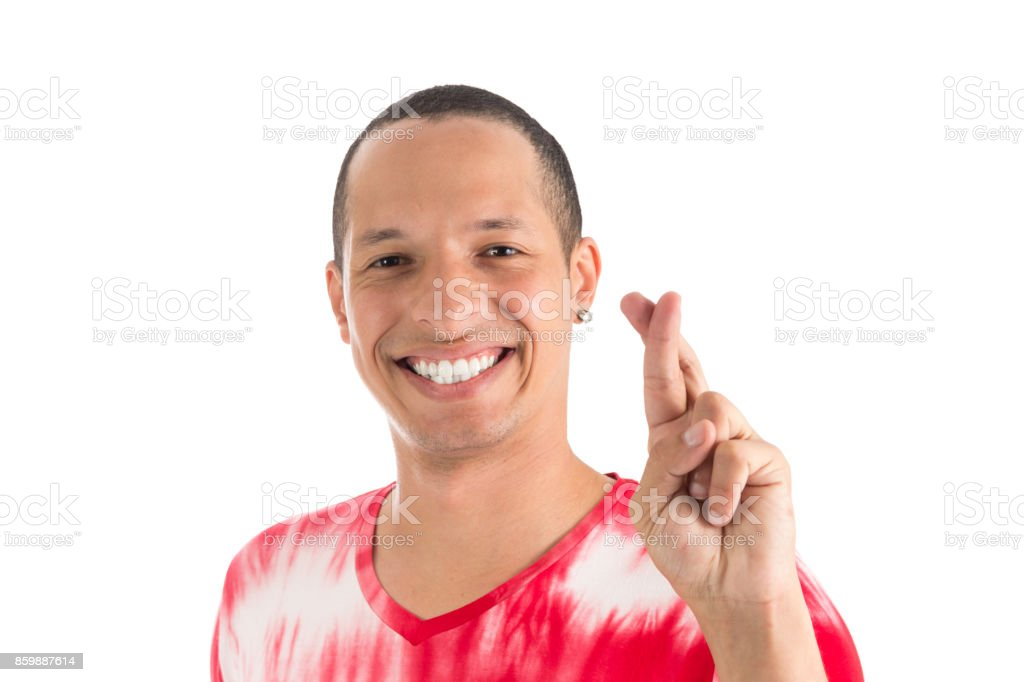 Smiling man with crossed fingers. Good luck, good fortune. Young latin american man wearing white and red shirt. White background. stock photo
