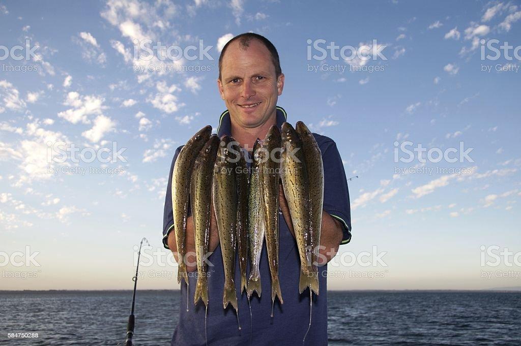 Smiling man with fish - foto de acervo