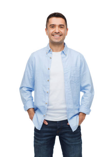 smiling man with hands in pockets stock photo