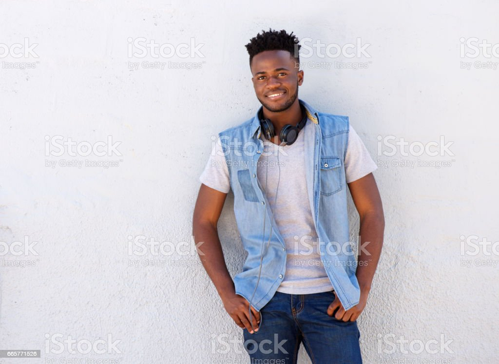 smiling man with headphones standing against white wall stock photo