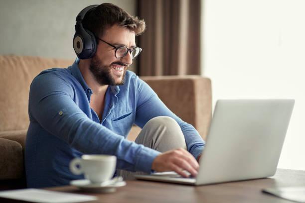 Lächelnder Mann mit Kopfhörern mit Laptop in seinem Haus – Foto