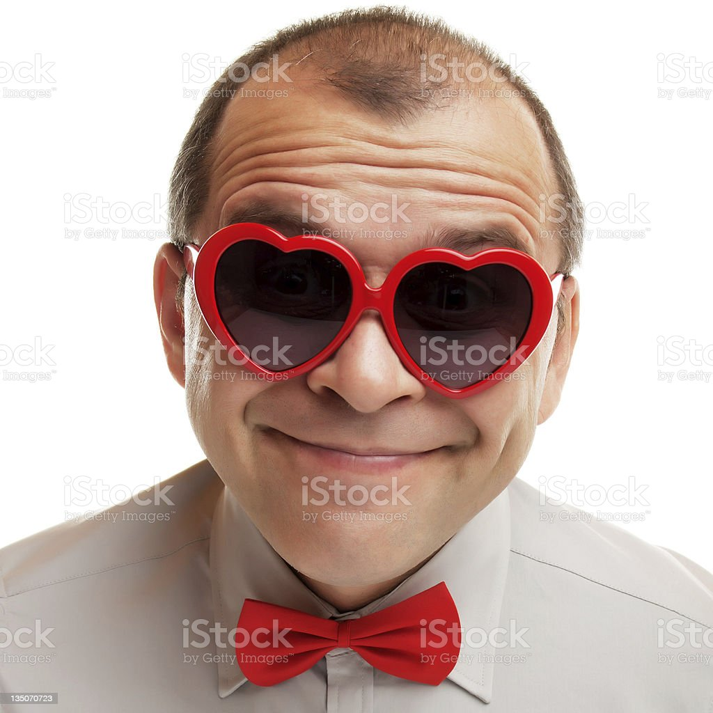 Smiling man with heart shaped sunglasses stock photo