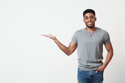 Smiling african-american man demonstrate something on his empty palm, white studio background, copy space