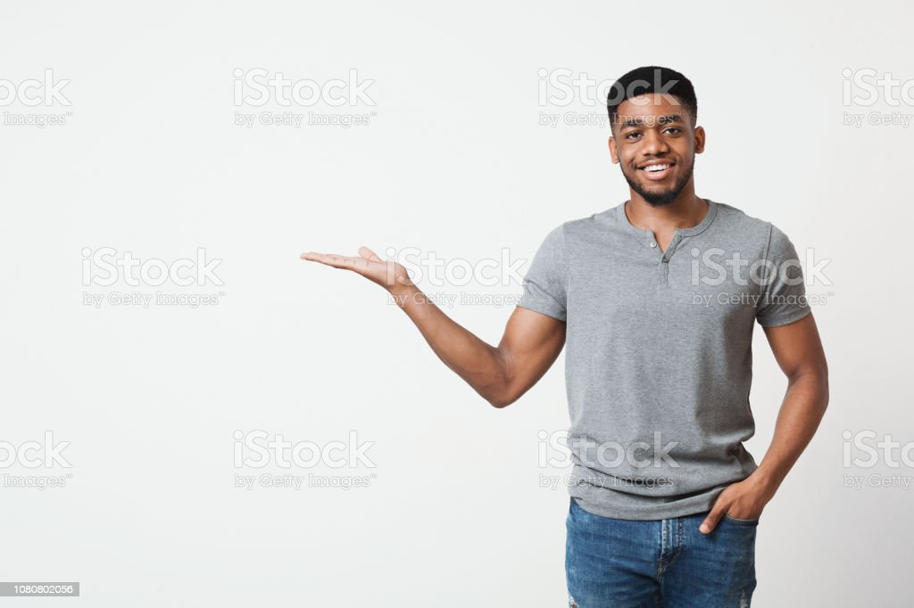 Smiling man with his palm up on white background stock photo