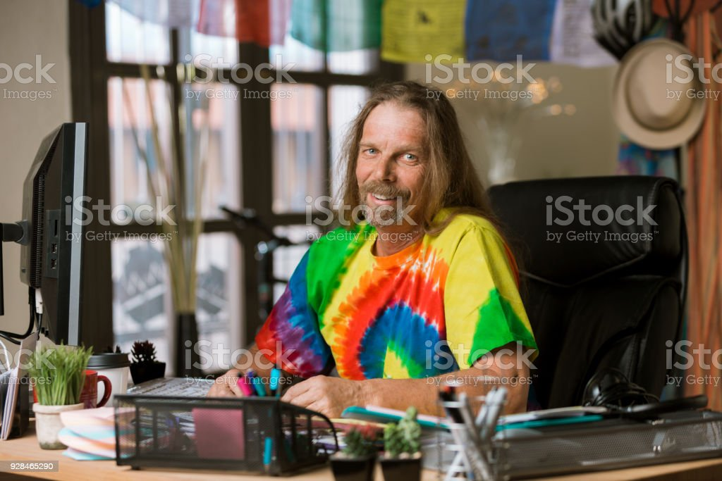 Smiling Man with Long Hair in a Colorful Office stock photo