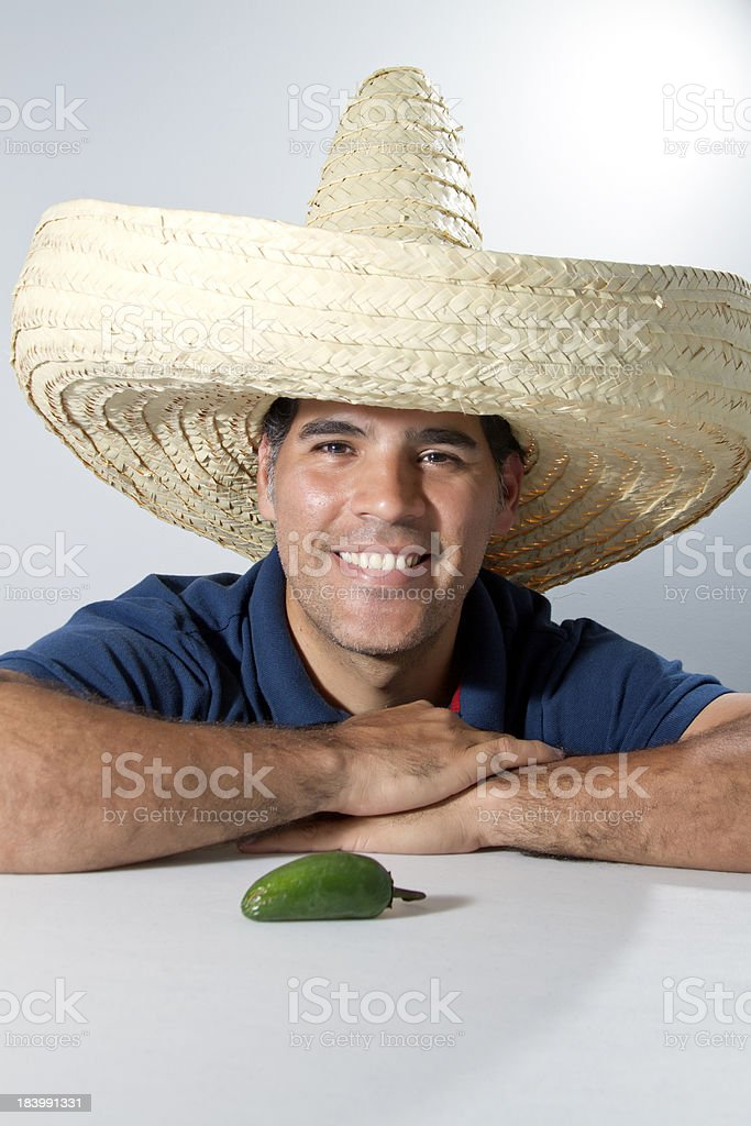 Smiling man with Mexican hat and hot pepper on table royalty-free stock photo