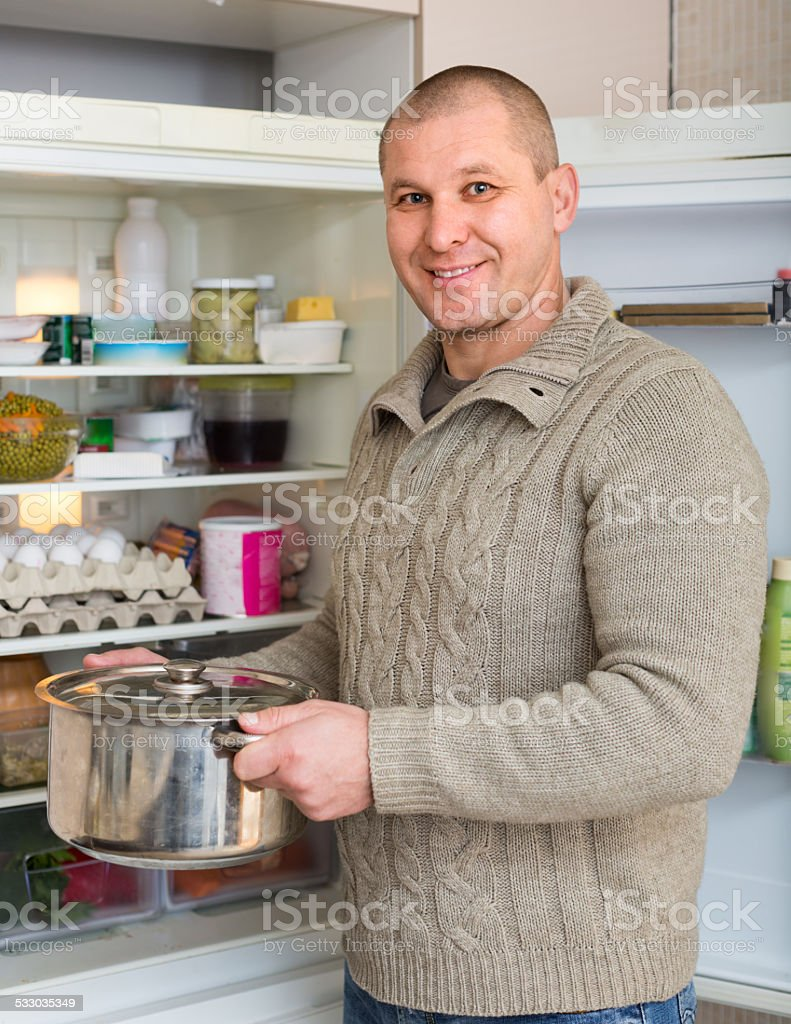 Smiling man with pan near fridge royalty-free stock photo