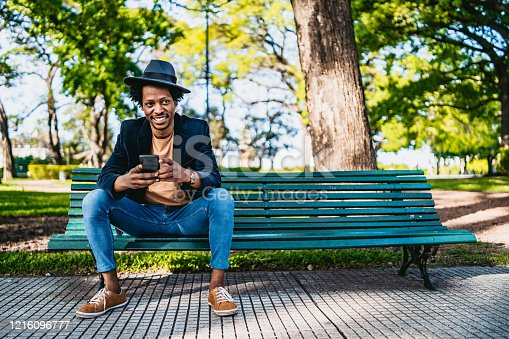 Smiling young African man using smartphone on park bench.