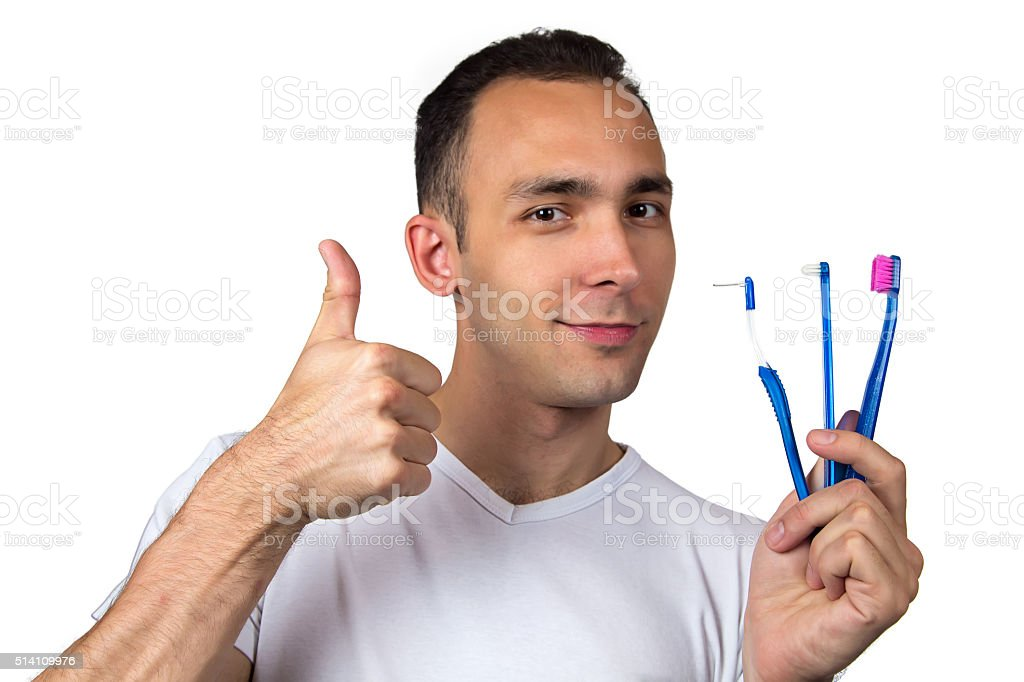 Smiling man with toothbrushes stock photo