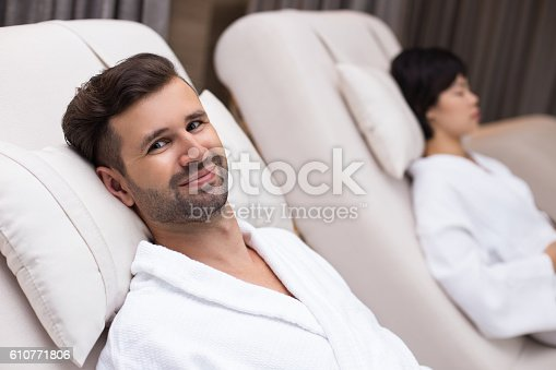610769340istockphoto Smiling Man with Woman Relaxing on Loungers in Spa 610771806