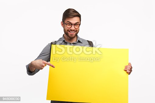 istock Smiling man with yellow banner 945069230