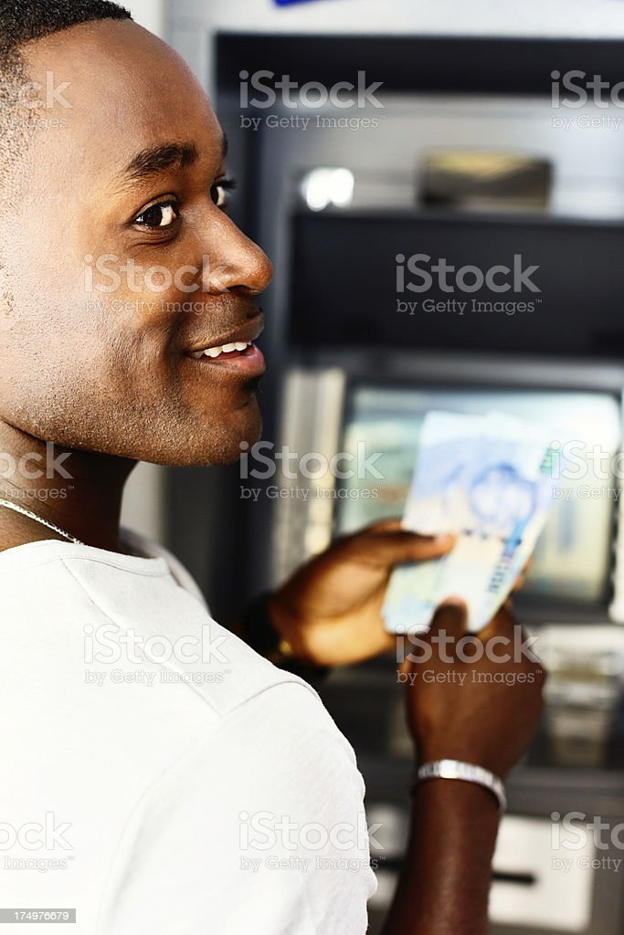 Smiling man withdraws money from cash machine stock photo