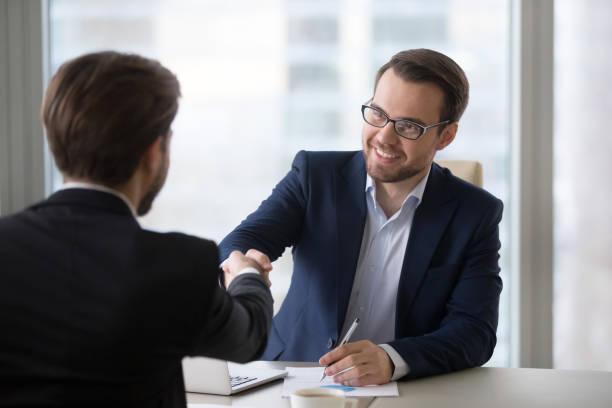glimlachend manager handshaking client aanvrager op vergadering of sollicitatiegesprek - juridisch beroep professioneel beroep stockfoto's en -beelden