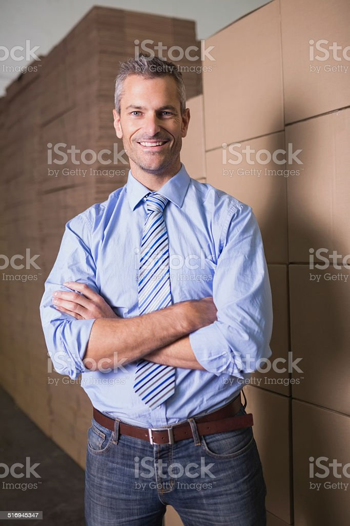 Smiling manager with arms crossed in warehouse stock photo