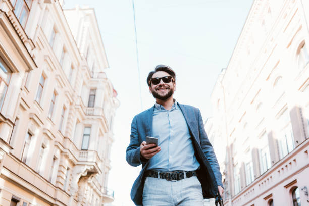 Smiling manager with stubble walking on the street with bag and mobile phone in hands stock photo