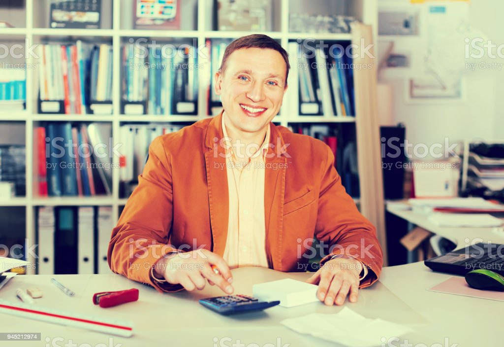 Smiling manager working at office desk stock photo