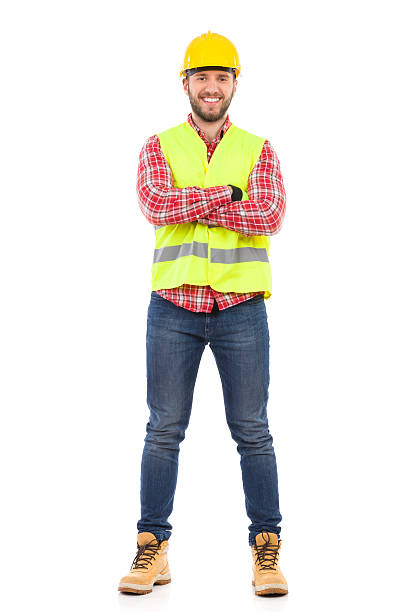 Smiling manual worker Smiling construction worker in yellow helmet and lime waistcoat posing with arms crossed. Full length studio shot isolated on white. reflective clothing stock pictures, royalty-free photos & images