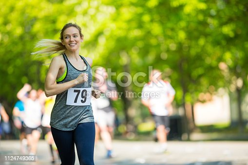 happy smiling young woman jogging at running event on sunny day in spring, shallow focus on female runner, background blurred