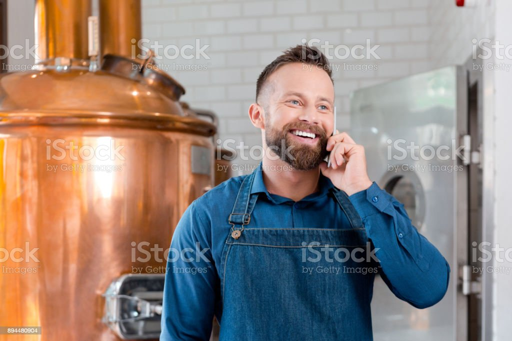 Smiling master brewer using phone in microbrewery Smiling master brewer talking on cell phone in beer manufacturing factory. Mature man talking on mobile phone in his microbrewery. Adult Stock Photo