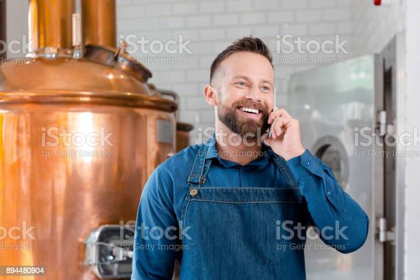 Smiling Master Brewer Using Phone In Microbrewery Stock Photo - Download Image Now