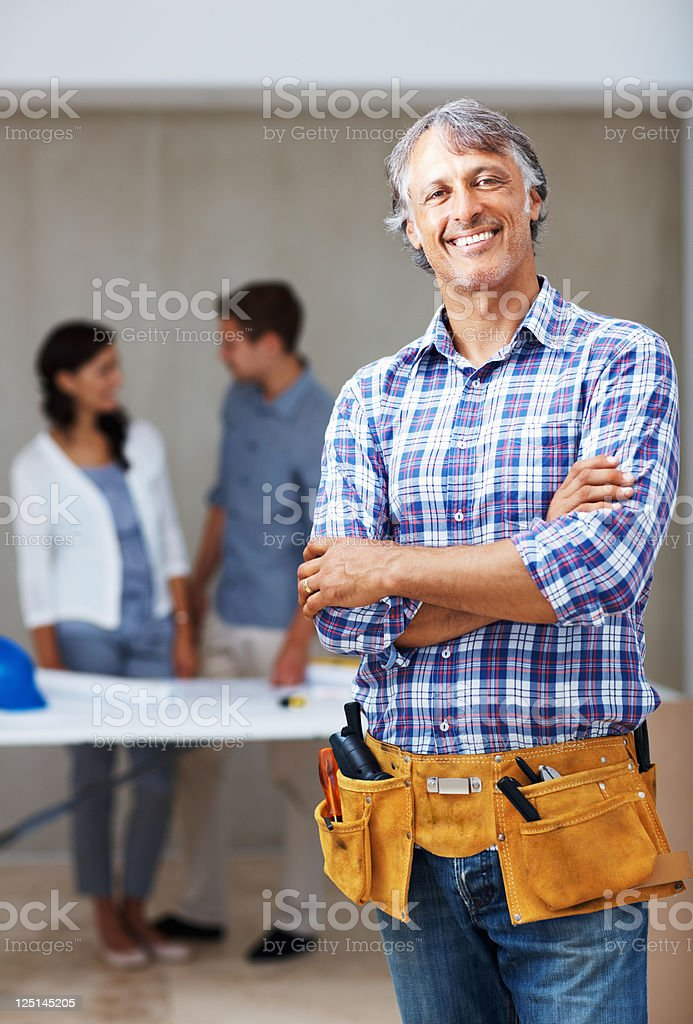Smiling, mature architect with clients in the background royalty-free stock photo