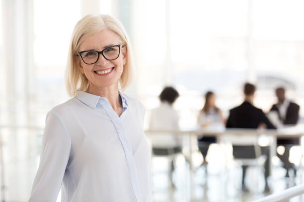 Smiling mature attractive businesswoman in glasses looking in camera Smiling mature attractive businesswoman in glasses looking in camera, happy friendly middle aged female executive, older team leader or business coach mentor posing in office, headshot portrait director stock pictures, royalty-free photos & images
