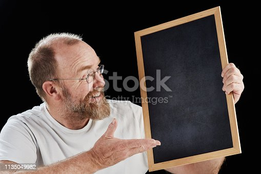 A genial mature man i beard and eyeglasses smiles as he points towards a blank chalkboard he holds.