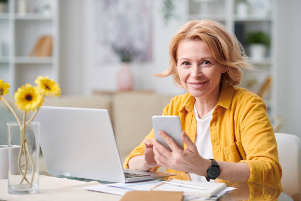 smiling mature blond businesswoman with smartphone looking at you - senior business woman tablet imagens e fotografias de stock
